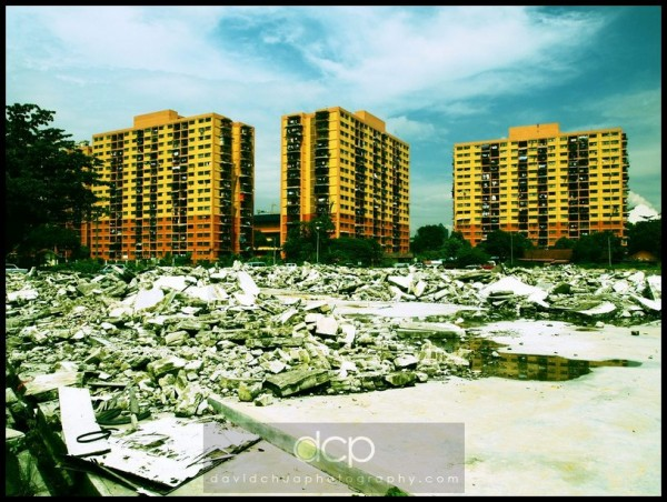 Uncleared mess from a torn-down building with apartment flats in the background